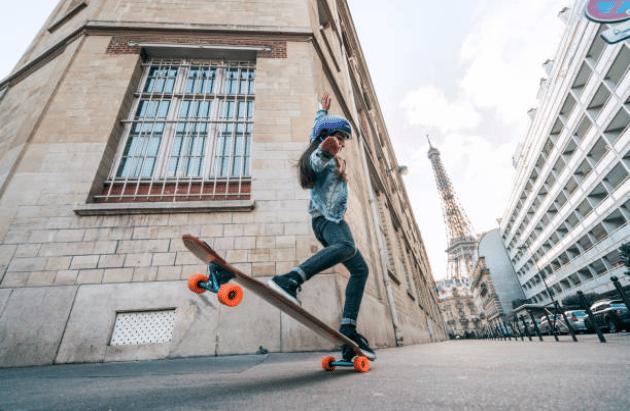 Femme qui fait une figure acrobatique sur une planche de skate dans les rues de Paris