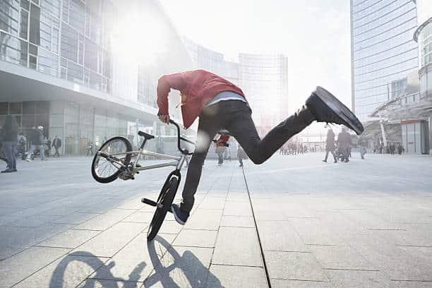 Homme qui fait une figure acrobatique sur un vélo BMX en pleine ville